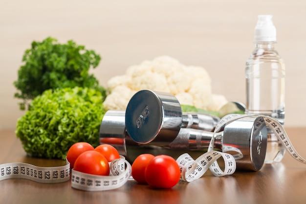 Manubri con nastro di misurazione, verdura e frutta isolati su sfondo di legno