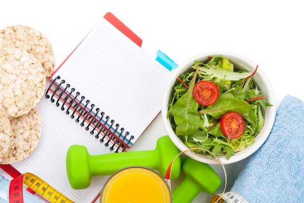 Manubri, metro a nastro, cibo sano e blocco note per lo spazio della copia. forma fisica e salute. isolato su sfondo bianco
