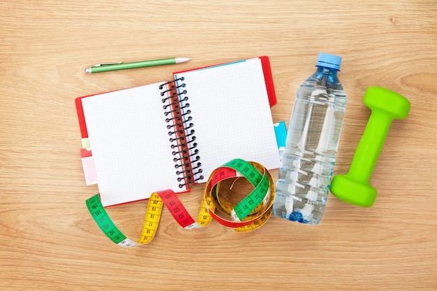 Manubri, metro a nastro, bottiglia d'acqua e blocco note per lo spazio della copia. fitness e salute
