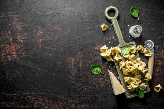 Gnocco crudo con parmigiano e spinaci. sul tavolo rustico scuro
