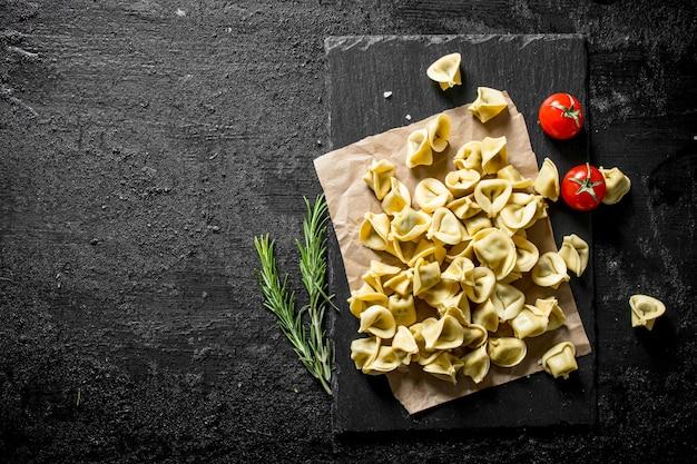 Gnocco crudo con rosmarino e pomodori sulla tavola rustica nera.