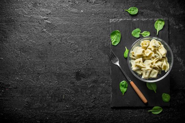Gnocchi in una ciotola con foglie di spinaci.