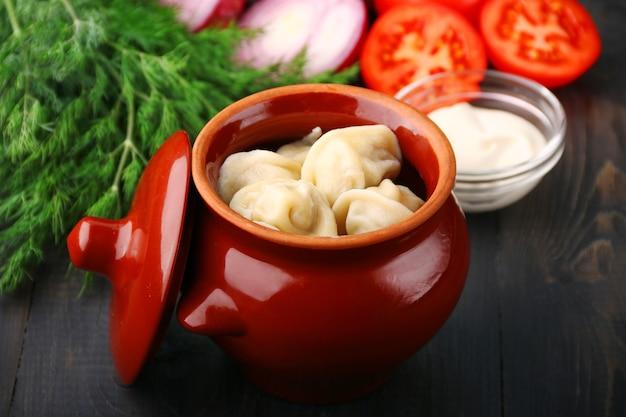 Gnocchi in una pentola verdure e panna acida. pelmeni russi, gnocchi con carne.