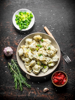 Gnocchi con carne di manzo, cipolle tritate, concentrato di pomodoro e rosmarino sul tavolo rustico scuro