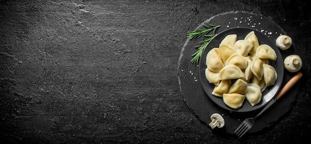 Gnocchi con carne di manzo su un piatto. su sfondo nero rustico