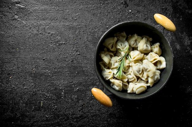 Gnocchi con carne di manzo in una pentola sulla tavola rustica nera.