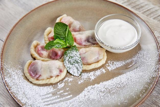 Gnocchi con ripieno di bacche, con panna acida stesa su un piatto decorato con foglie di menta