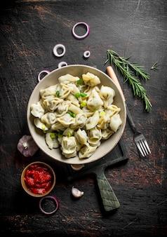 Gnocchi con aglio, anelli di cipolla e concentrato di pomodoro sul tavolo rustico scuro
