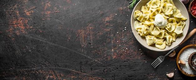 Gnocchi con panna acida e spezie. su fondo rustico scuro