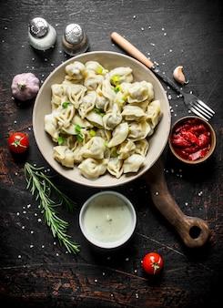 Gnocchi con spezie, aglio, panna acida e concentrato di pomodoro sul tavolo rustico scuro.