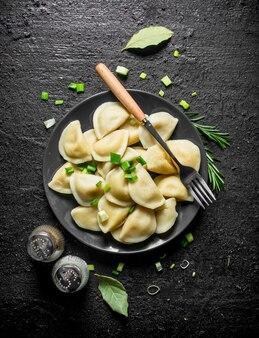 Gnocchi con spezie, rosmarino e cipolle verdi sulla tavola rustica nera.