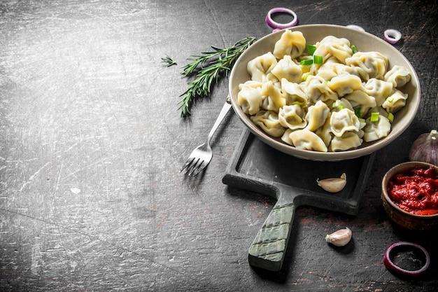 Gnocchi con concentrato di pomodoro, spicchi d'aglio e rosmarino scuro sul tavolo rustico
