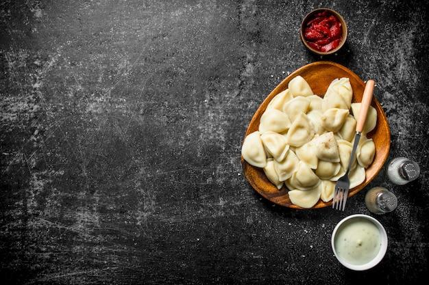 Gnocchi con concentrato di pomodoro, panna acida e spezie. su fondo rustico scuro