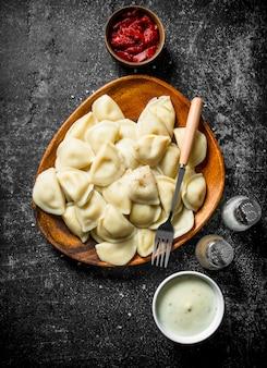 Gnocchi con concentrato di pomodoro, panna acida e spezie sul tavolo rustico scuro