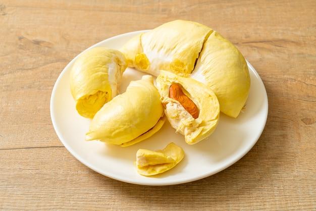 Durian stagionato e fresco, buccia di durian su piatto bianco