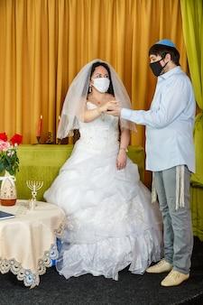 Durante una cerimonia di chuppah a un matrimonio ebraico in una sinagoga, lo sposo mette un anello all'indice della sposa mentre indossa una maschera protettiva. foto verticale