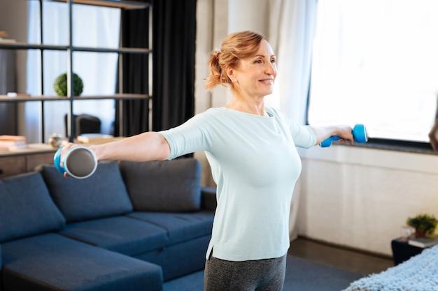 Durante l'allenamento mattutino. allegra donna matura dai capelli chiari che rimane in soggiorno e porta manubri blu