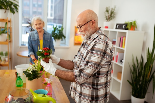 Durante il lavoro. simpatico uomo anziano che indossa guanti bianchi mentre lavora in giardino