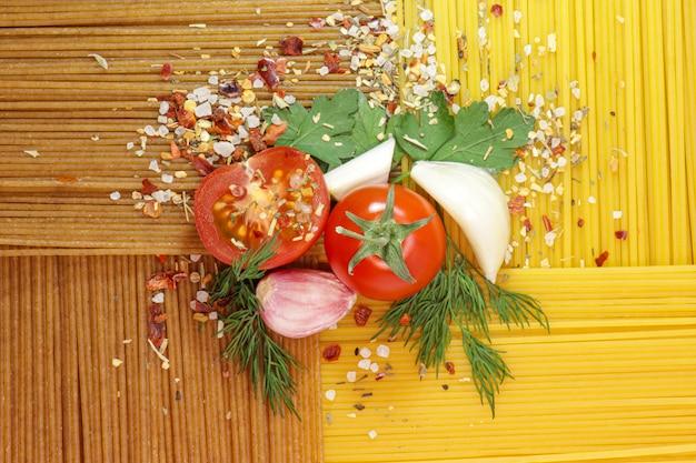 Spaghetti di grano duro e pomodorini maturi, aglio e spezie. verdure fresche. prodotti per cucinare una pasta deliziosa. il meglio