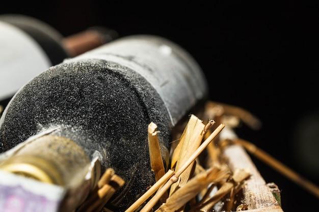 La polvere copre una nuova bottiglia di vino sdraiata sul fieno