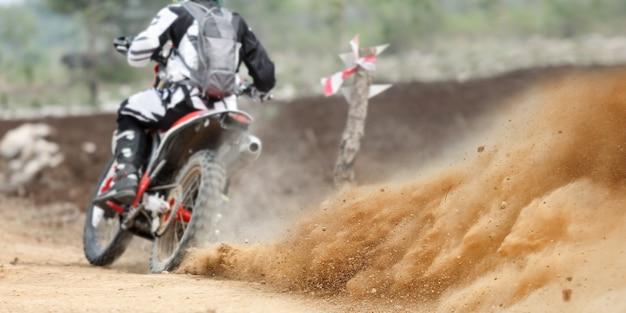 Spruzzi di polvere da gara di motociclette enduro