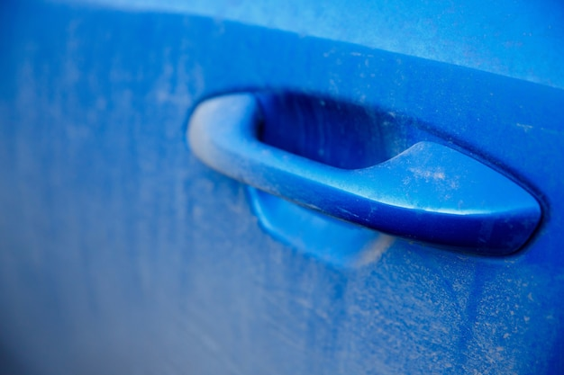 Maniglia della porta polverosa e sporca di un'auto blu