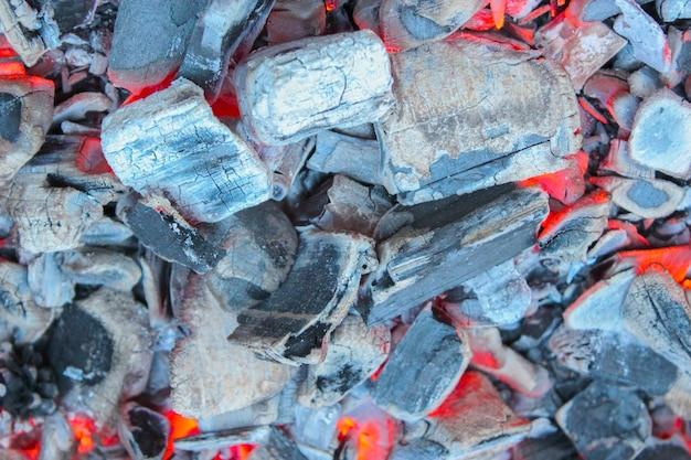 Le braci morenti nel primo piano del fuoco come sfondo