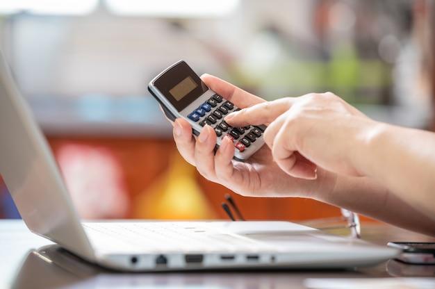 Concetto di e-commerce. la mano della persona che tiene la calcolatrice e inserisce i dati.