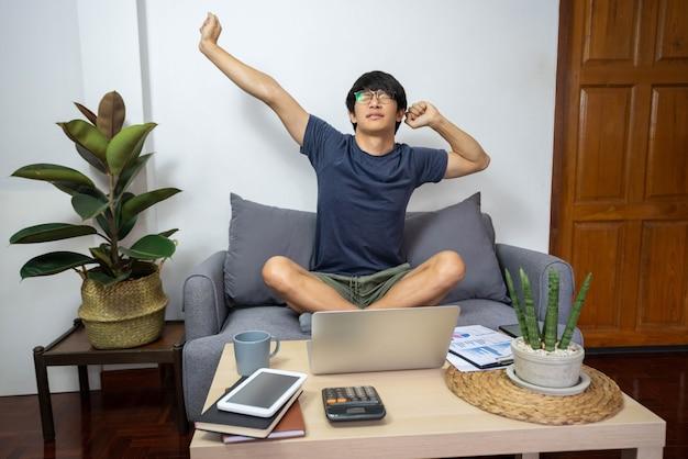 Concetto di e-commerce un uomo che indossa la t-shirt blu e i pantaloncini verdi che sembra stanco per aver lavorato a lungo.