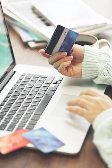 Concetto di e-commerce. donna con carta di credito e laptop, da vicino