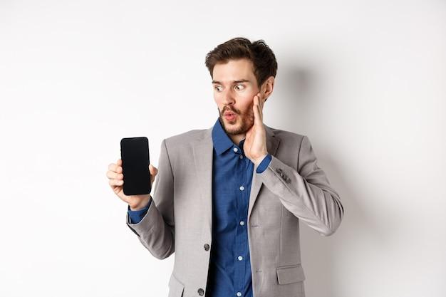 E-commerce e concetto di shopping online. manager maschio stupito in vestito guardando lo schermo del telefono cellulare con la faccia eccitata, in piedi su sfondo bianco.