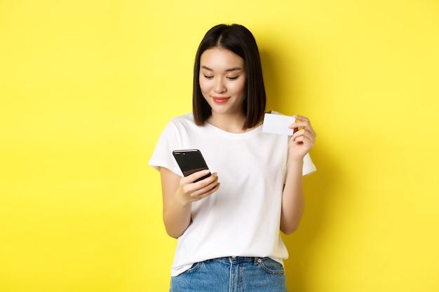 E-commerce e concetto di shopping online. bella donna asiatica che paga in internet, guardando lo schermo dello smartphone e tenendo la carta di credito in plastica, sfondo giallo.