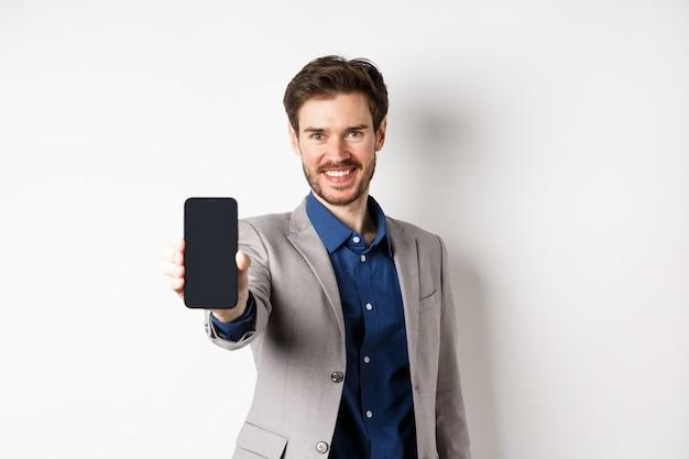 E-commerce e concetto di shopping online. fiducioso uomo d'affari in tuta allungare la mano con lo schermo vuoto dello smartphone, mostrando sul telefono, in piedi su sfondo bianco.