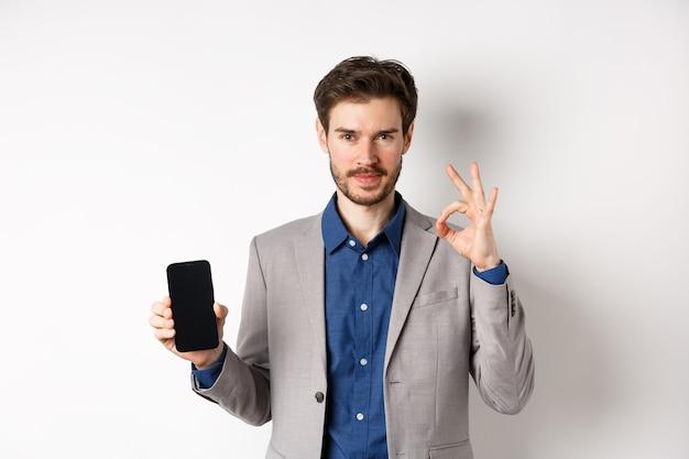E-commerce e concetto di shopping online. fiducioso bell'uomo d'affari in tuta che mostra il segno giusto e lo schermo vuoto dello smartphone, consiglia l'applicazione, sfondo bianco.