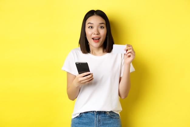 E-commerce e concetto di shopping online. eccitato ordine donna asiatica in internet, tenendo lo smartphone e la carta di credito in plastica, in piedi sopra il giallo.