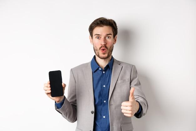 E-commerce e concetto di shopping online. imprenditore entusiasta consiglia l'app per le finanze, mostrando lo schermo vuoto dello smartphone e il pollice in alto, sfondo bianco.