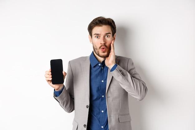 E-commerce e concetto di shopping online. uomo emozionante senza fiato stupire e mostrando lo schermo vuoto dello smartphone, indossando tailleur, sfondo bianco.