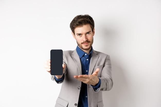 E-commerce e concetto di shopping online. l'uomo ti ha mostrato lo schermo vuoto dello smartphone, mostrando il display del telefono per introdurre qualcosa, in piedi su sfondo bianco.