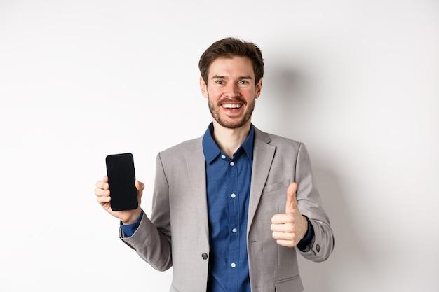 E-commerce e concetto di shopping online. imprenditore soddisfatto in tuta che mostra lo schermo vuoto dello smartphone e il pollice in su, elogi un buon affare, sfondo bianco.