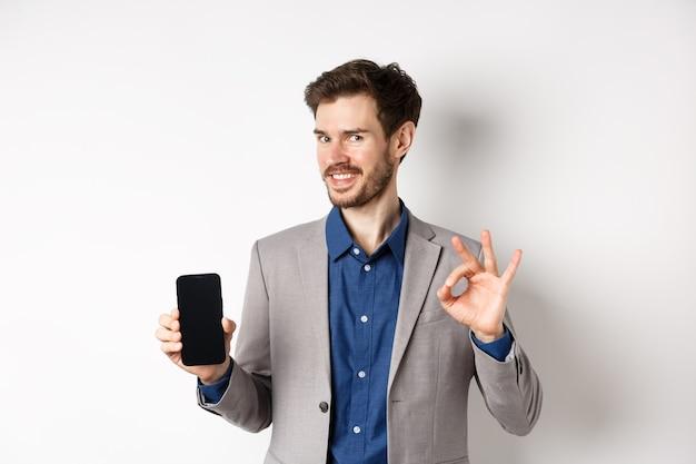 E-commerce e concetto di shopping online. l'uomo d'affari sorridente mostra il segno giusto e lo schermo vuoto dello smartphone, dimostra il suo account, in piedi su sfondo bianco.