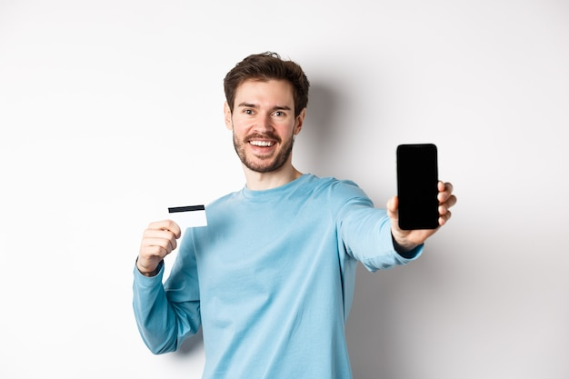 E-commerce e concetto di acquisto. sorridente uomo caucasico che mostra la carta di credito in plastica e lo schermo vuoto dello smartphone, consigliando app online, sfondo bianco.
