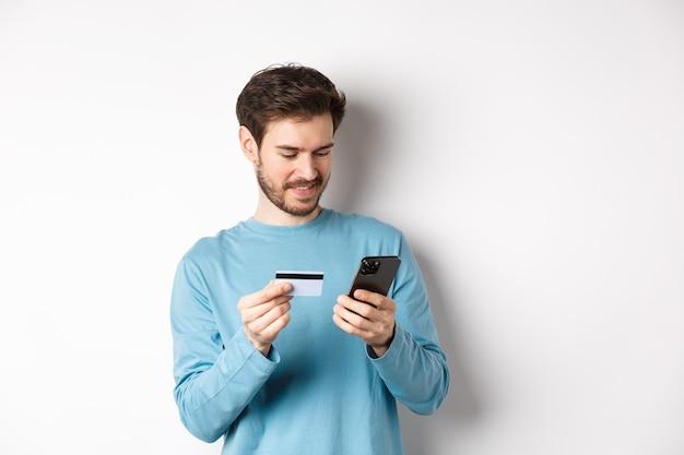 E-commerce e concetto di acquisto. uomo sorridente ordina online, copia il numero di carta di credito nell'app del telefono cellulare, in piedi su sfondo bianco.
