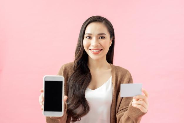 E-commerce, shopping e concetto di lifestyle. la ragazza asiatica ha trovato un'applicazione fantastica per lo shopping online, il monitoraggio degli ordini, il telefono cellulare in mano, lo schermo e la carta di credito