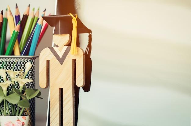 E-learning online torna al concetto di scuola, la gente firma il legno con la graduazione nera che celebra il cappuccio sullo schermo del computer vicino alla scatola delle matite. studio alternativo ovunque e in qualsiasi momento formazione universitaria a distanza