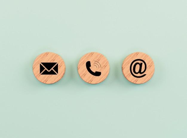 L'indirizzo e-mail, il numero di telefono e le icone delle lettere stampano lo schermo su un blocco di legno circolare su sfondo verde per il contatto aziendale della pagina web e il concetto di servizio clienti tramite rendering 3d.