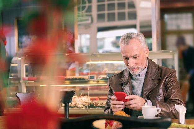 Posta elettronica sul telefono. uomo francese maturo che si sente occupato mentre controlla la posta elettronica di lavoro sul telefono che si siede nel forno