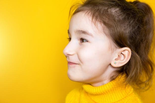 Piercing all'orecchio in un bambino - una ragazza mostra un orecchino all'orecchio fatto di una lega medica. sfondo giallo, ritratto di una ragazza di profilo.