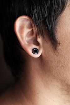 Piercing all'orecchio, ragazzo con un tunnel nero nell'orecchio.