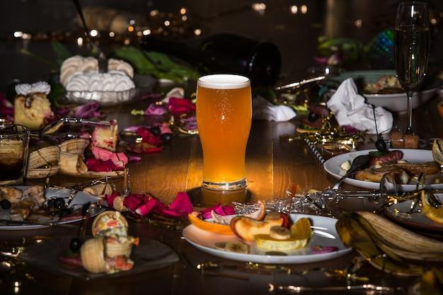 La mattina presto dopo la festa bicchiere di birra chiara scura sul tavolo con coriandoli