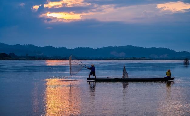 La mattina presto prima dell'alba, un pescatore asiatico su una barca di legno getta una rete per catturare pesci d'acqua dolce in un fiume naturale.